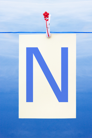 Seamless washing line with paper against a blue sky showing the letter N photo