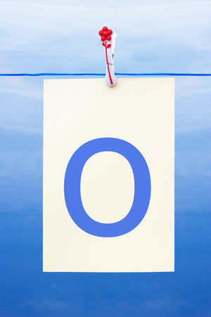 Seamless washing line with paper against a blue sky showing the letter o Stock Photo