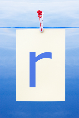 Seamless washing line with paper against a blue sky showing the letter r