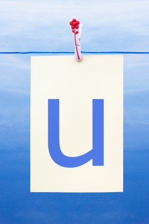 Seamless washing line with paper against a blue sky showing the letter u Stock Photo