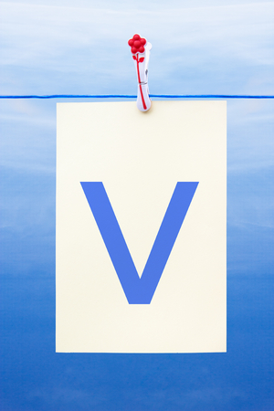 Seamless washing line with paper against a blue sky showing the letter v