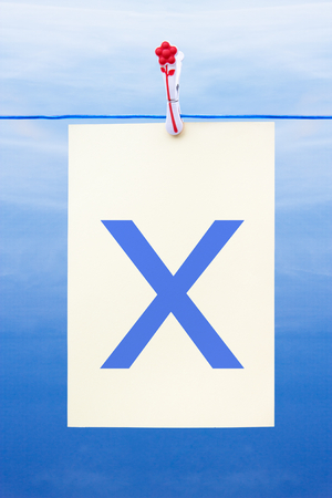 Seamless washing line with paper against a blue sky showing the letter x Stock Photo