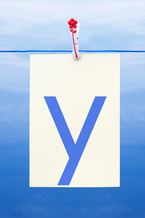 Seamless washing line with paper against a blue sky showing the letter y