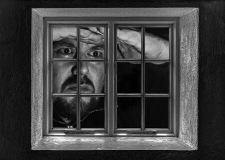prodigious: Man giant looking through a window at night Stock Photo