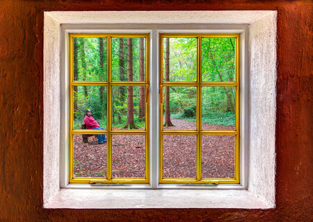 Man sitting outside in a forest seen through a window photo
