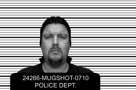 booked: Mugshot of a man at a police department
