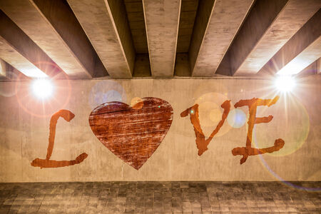 The word love with heart painted as graffiti on the support column of an overpass photo