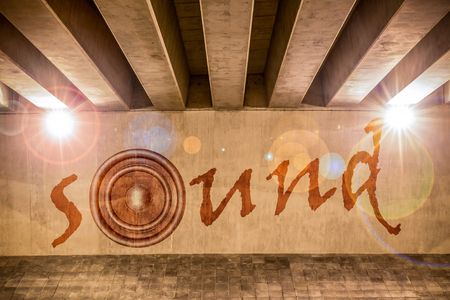 underpass: The word sound with bass speaker as graffiti on the support column of an overpass