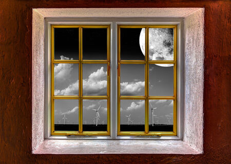 View through a window of a wind turbine farm at night with a full moon photo