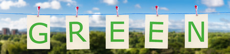 Panorama of a clothes line with the word green with a backdrop of blue sky and a forest photo