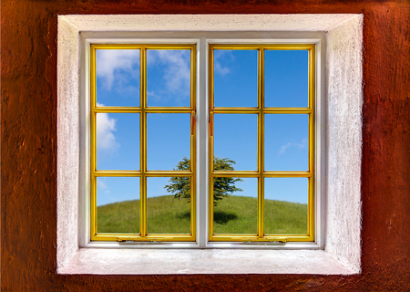 View of a hill with a tree through a window photo