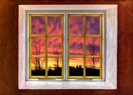 View of a purple orange sunset through a window photo