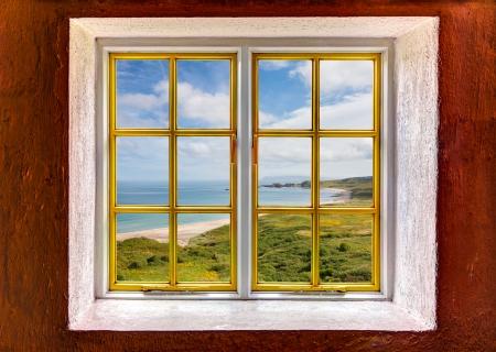 adentro y afuera: Vista de la playa y de las dunas y el océano a través de una ventana Foto de archivo