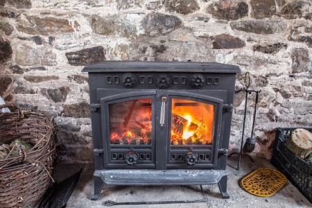 Cast iron stove burning wood logs against a robust stone wall Stockfoto
