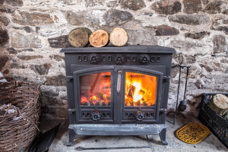 Cast iron wood stove burning logs against a robust stone wall Stockfoto