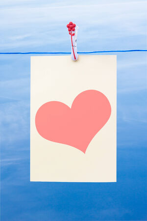 Piece of paper with heart on a washing line against a blue sky photo