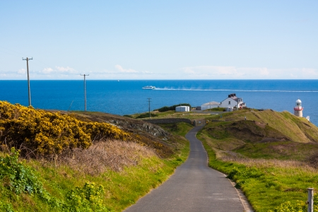 The road towards the Baily Lighthouses on Howth cliffs in Ireland on a sunny day photo