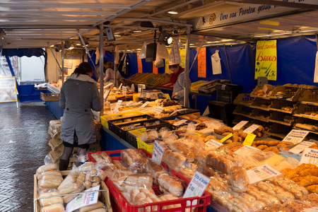 street market: ZWOLLE, THE NETHERLANDS - FEBRUARY 1, 2014: Unidentified woman buying bread at the street market in Zwolle Editorial