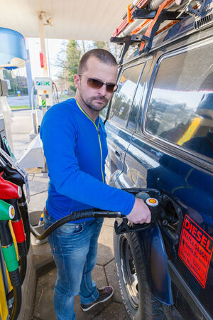 fueling: ZWOLLE, THE NETHERLANDS - FEBRUARY 3, 2014: Unidentified man filling up a Toyota Land Cruiser with diesel at a Shell gas station. Shell have 44,000 service stations worldwide. Editorial