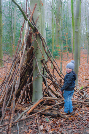 tipi: Little kid building a tipi on a winter day
