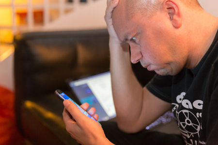 Man reading bad news on his smartphone with laptop in background photo