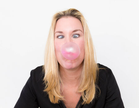 Young woman blowing bubblegum with crossed eyes photo