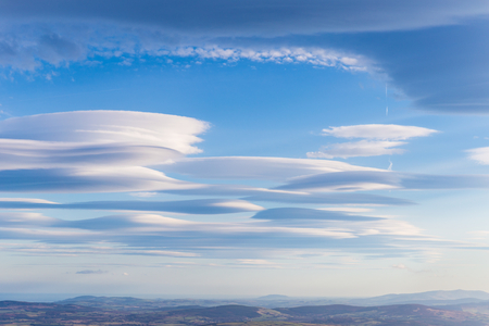 lenticular cloud: Lenticular clouds forming in the troposphere