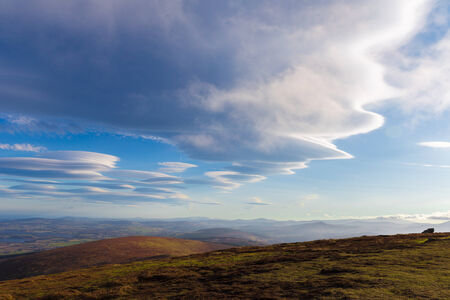 lenticular: Lenticular clouds forming in Wicklow Mountains Stock Photo