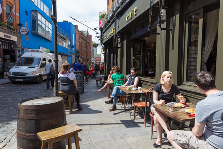 DUBLIN - MAY 17, 2014: Temple Bar in Dublin city is a popular tourist destination. People eating lunch at a Dublin cafe.