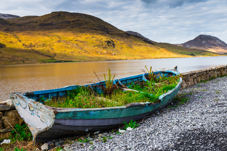 lough: Overgrown rowboat at the shore of Kylemore Lough in Connacht Stock Photo