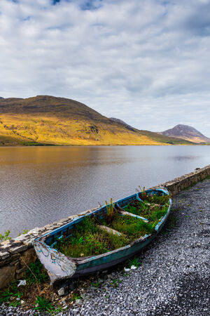 scruffy: Overgrown rowboat at the shore of Kylemore Lough in Connacht Stock Photo