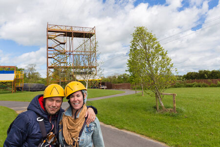 Young couple in front of a zip line drop off point Stock Photo