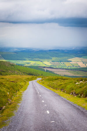 leinster: Road downhill from Mount Leinster on a cloudy day Stock Photo