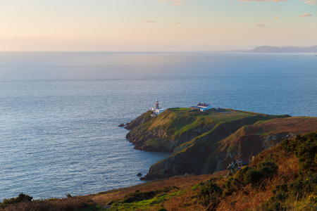 Howth cliffs with helipad and Baily Lighthouse at golden hour photo