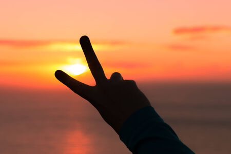 orange sign: One hand making a peace sign at golden hour sunset