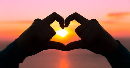 Panoramic image of two hands forming a heart symbol at golden hour sunset photo