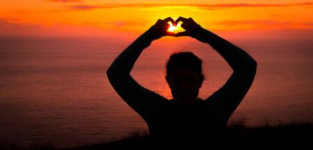 position d amour: Femme silhouette formant un symbole du c?ur au Golden Sunset heures