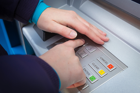 whilst: Woman covering her hands whilst entering her PIN at an ATM Stock Photo