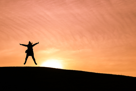 spreading arms: Woman jumping in the air and spreading arms and legs against a setting sun