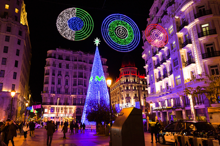 MADRID, SPAIN - DECEMBER 31, 2014: Calle de la Montera crowded with tourists on December 31 in Madrid. A big illuminated Christmas tree and festive decorations light up the street each year for the holidays in Madrid, the capital city of Spain. Editorial
