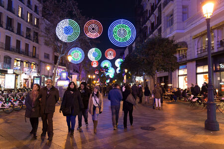 strolling: MADRID, SPAIN - DECEMBER 31, 2014: Calle de la Montera crowded with tourists on December 31 in Madrid. Festive decorations light up the street each year for the holidays in Madrid, the capital city of Spain.