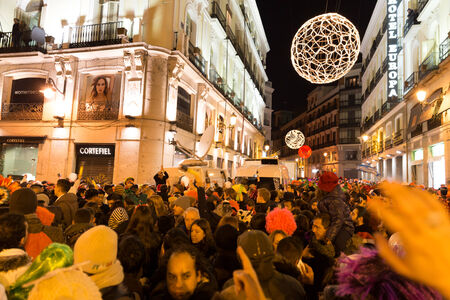 live event: MADRID, SPAIN - DECEMBER 31, 2014: The famous Puerta del Sol crowded with tourists on December 31 in Madrid. A TV crew is filming the live event. Editorial