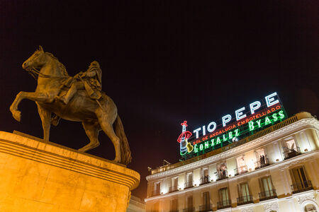 to pepe: MADRID, SPAIN - DECEMBER 31, 2014: T?o Pepe sign and Monument to King Charles III at Puerta del Sol on December 31 in Madrid. Cameras situated on the balconies are set up to film New Year celebrations