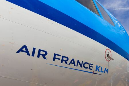 klm: AMSTERDAM - 19 JULY, 2014: The Air France KLM company name written on a Cityhopper Fokker 70 with reflection of boarding travellers.