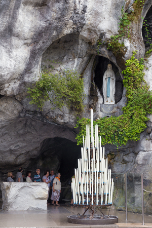 sanctuary: LOURDES - JULY 23, 2014: Candles displayed at the cave at Massabielle in Lourdes, where St. Bernadette Soubirous claimed to have seen the Blessed Virgin Mary. It now is a religious grotto.
