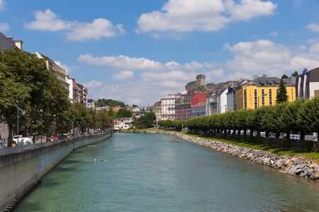 tributary: LOURDES, FRANCE - JULY 23, 2014: The Gave de Pau river in Lourdes. It is a river in south-western France and a left tributary of the Adour. It takes its name from the city Pau, through which it flows. Editorial