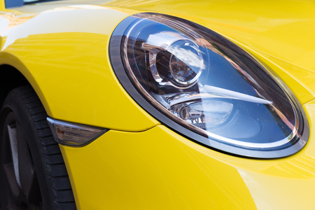 characteristic: TOULOUSE, FRANCE - JULY 22, 2014: Parked bright yellow Porsche 911 with characteristic oval shaped headlights.