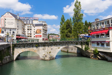 gave: LOURDES, FRANCE - JULY 23, 2014: The Old Bridge called Pont Vieux spans the Gave de Pau river in Lourdes. The road leads to The castle fort of Lourdes. Editorial