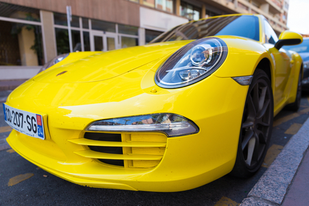 yellow car: TOULOUSE, FRANCE - JULY 22, 2014: Parked bright yellow Porsche 911 with characteristic oval shaped headlights.
