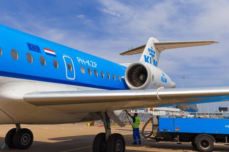 refilling: AMSTERDAM - 19 JULY, 2014: An Air France KLM Cityhopper Fokker 70 is being refuelled before the flight to Toulouse.
